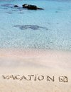 Vacation and checked mark written on sand on a beautiful beach blue waves in background Stock Photo