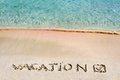 Vacation and checked mark written on sand on a beautiful beach blue waves in background Royalty Free Stock Photos