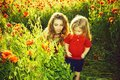 Vacation in the country. mothers day, girl and little boy in field of poppy Royalty Free Stock Photo