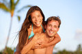 Vacation couple fun on beach man giving piggyback men ride piggybacking women girlfriend beautiful interracial in Royalty Free Stock Image