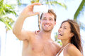 Vacation couple taking pictures with camera phone on beach romantic photographing self portrait having fun on summer Royalty Free Stock Photography