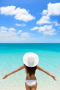 Vacation freedom woman on luxury tropical getaway happy beach carefree destination wearing a white sun hat from behind with arms Stock Photography