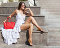 A girl in a light outfit with sunglasses and a cool big red fashionable handbag on a hot summer day sits on stone stunts Royalty Free Stock Photo
