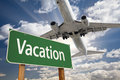 Vacation Green Road Sign and Airplane Above Royalty Free Stock Photo