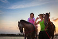 Vacation lifestyles couple horseback riding at sunset Stock Image