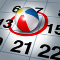 Vacation planning and plan your trip with a beach ball on a calendar with a red highlight circle as a symbol of fun time Royalty Free Stock Image