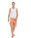 On vacation smiling young man in shorts walking Royalty Free Stock Photos