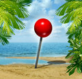 Vacation spot and holiday travel planning search concept with a location red pushpin on a tropical sandy beach as a metaphor for Royalty Free Stock Images