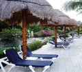 Vacation spots near water plank beds and chaise lounges under straw umbrellas Stock Image
