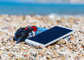 Vacation time, smart phone, car keys and cigarettes, on the seashells in the beach Royalty Free Stock Photo