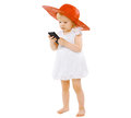 Vacation travel technology and people concept little girl lady child in a red hat white dress speaks on the phone Royalty Free Stock Images