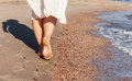 Vacation travel - woman leg closeup walking on white sand relaxing in beach cover-up pareo beachwear. and tanned legs. Sunmme Royalty Free Stock Photo
