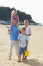 Vacationing family standing on beach full length portrait of a sand at Stock Photo