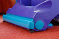 Vacuum cleaning close up of a blue cleaner on a red carpet Stock Photo