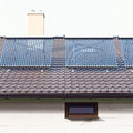 Vacuum solar water heating system on a house roof. Royalty Free Stock Photo