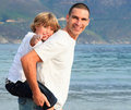 image photo : Father giving his son piggyback ride on the beach