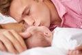 Vader kissing baby girl aangezien zij samen in bed liggen Royalty-vrije Stock Fotografie