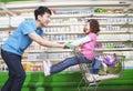Vader pushing daughter in boodschappenwagentje binnen supermarkt het lachen Stock Fotografie