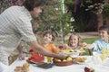 Vader serving pineapple slices aan jonge geitjes bij openluchtlijst Stock Foto