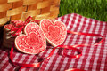 Valentine cookies picnic basket heart shaped on red and white checked cloth and leaning against wicker green grass in background Stock Image