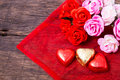 Valentine decoration heart shaped chocolate and roses on wooden table top Stock Photos
