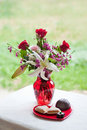 Valentine flowers in red vase and sweets Royalty Free Stock Images