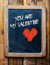 Valentine message on vintage chalkboard style over old wood background with the you are my written in white chalk next to a red Royalty Free Stock Photo