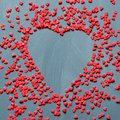 Valentine`s card concept with sweet red hearts sprinkling on gray background. Copy space. View from above. Royalty Free Stock Photo