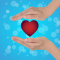 Valentine s day background female hands with a red heart on a blue bokeh Royalty Free Stock Images