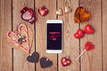 Valentine's day background with smartphone mock up and heart shapes on wooden table. Royalty Free Stock Photo