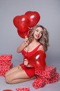 Valentine's Day. Beautiful happy woman with red heart balloons o