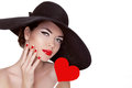 Valentine s day beautiful woman with heart in her hand wearing elegant hat makeup manicured nails beauty portrait of attractive Royalty Free Stock Photo
