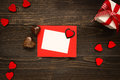 Valentine`s Day card on the wooden background. Gift box, red hearts and chocolate on the wooden desk.