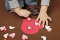 Valentine s day craft with hearts child doing heart stickers Royalty Free Stock Image