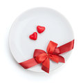 Valentine s day heart shaped candy over plate with red bow isolated on white background Royalty Free Stock Photography