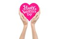 Valentine's Day and love theme: hand holds a greeting card in the form of a pink heart with the words Happy Valentine's day