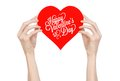 Valentine's Day and love theme: hand holds a greeting card in the form of a red heart with the words Happy Valentine's day