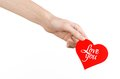 Valentine's Day and love theme: hand holds a greeting card in the form of a red heart with the words Love you isolated