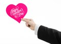 Valentine's Day and love theme: man's hand in a black suit holding a card in the form of a pink heart