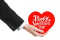 Valentine's Day and love theme: man's hand in a black suit holding a card in the form of a red heart