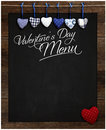 Valentine s day menu chalkboard blue and red gingham love hearts hanging on wooden frame with blackboard dotted heart in Royalty Free Stock Images