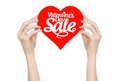 Valentine s day and sale topic hand holding a card in the form of a red heart with the word sale isolated on white background Stock Photo