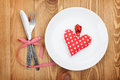 Valentine s day toy heart over plate with silverware on wooden table background Royalty Free Stock Photos