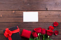 Valentine's Day: White empty paper card, red roses, gold ring and box gift with ribbon Royalty Free Stock Photo