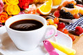 Valentines breakfast for a sweetheart with cup of fresh coffee and spoon tied with pink bow colorful roses and assorted fresh Royalty Free Stock Image