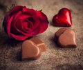 Valentines day background hearts chocolate and red roses on wooden board Royalty Free Stock Photography