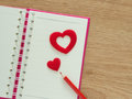 Valentines day background with red hearts, book for diary and color pencils on wood floor. Love and Valentine concept