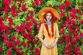 Valentines Day background. Retro girl with red lips in stylish yellow dress in dots in beautiful summer roses garden.