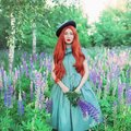 Valentines Day background. Young neat redhead girl with very long hair on lupine background. Valentines Day beauty woman