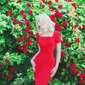 Valentines Day background. Young outstanding retro girl with red lips in stylish dress in beautiful summer roses garden.